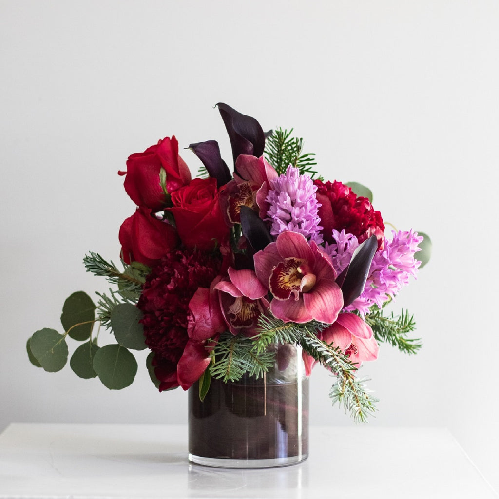Flower arrangement of avender hyacinth, plum calla lilies, red roses, cymbidium orchid blossoms and burgundy peonies