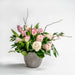 Flower arrangement with pink roses, blooming Quince, fragrant Freesia, Dutch tulips, ranunculus and fern