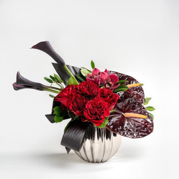 "Flower arrangement of ""Hearts"" roses, black ti leaves, cymbidium orchid blossoms, calla lilies and anthurium"