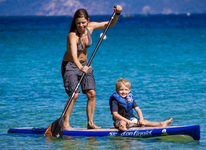 woman and little boy paddleboarding