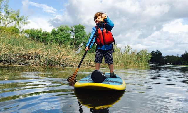 young child paddleboarding