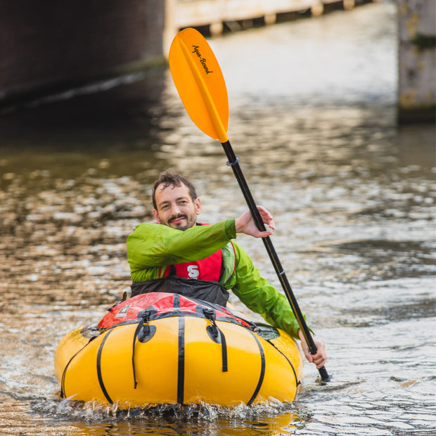 man packrafting in the city with a manta ray fiberglass kayak paddle