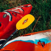 shred fiberglass whitewater kayak paddle laying on whitewater kayak