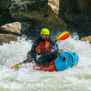 man packrafting on rapids down a river