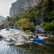 back of woman packrafting a river in Mexico