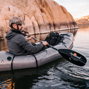 right side of man packrafting on a river