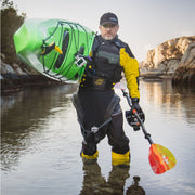 man holding a green kayak on his shoulder with a kayak paddle in the other hand