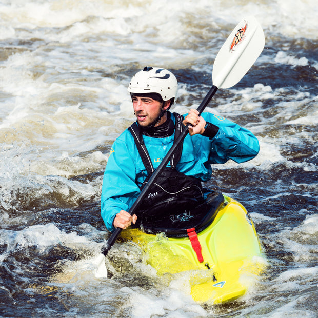 front view of man whitewater kayaking in some rapids
