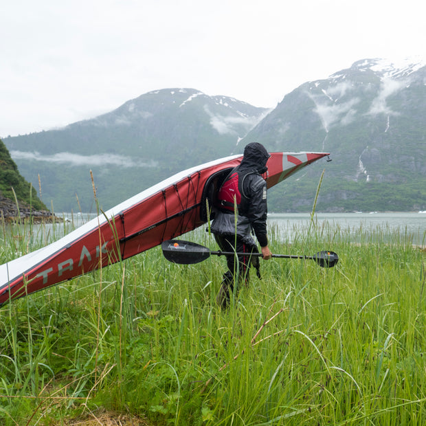 carrying a kayak and manta ray kayak paddle through a grassy field