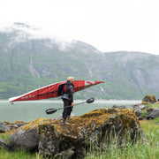 man standing on rock holding a kayak and manta ray carbon kayak paddle