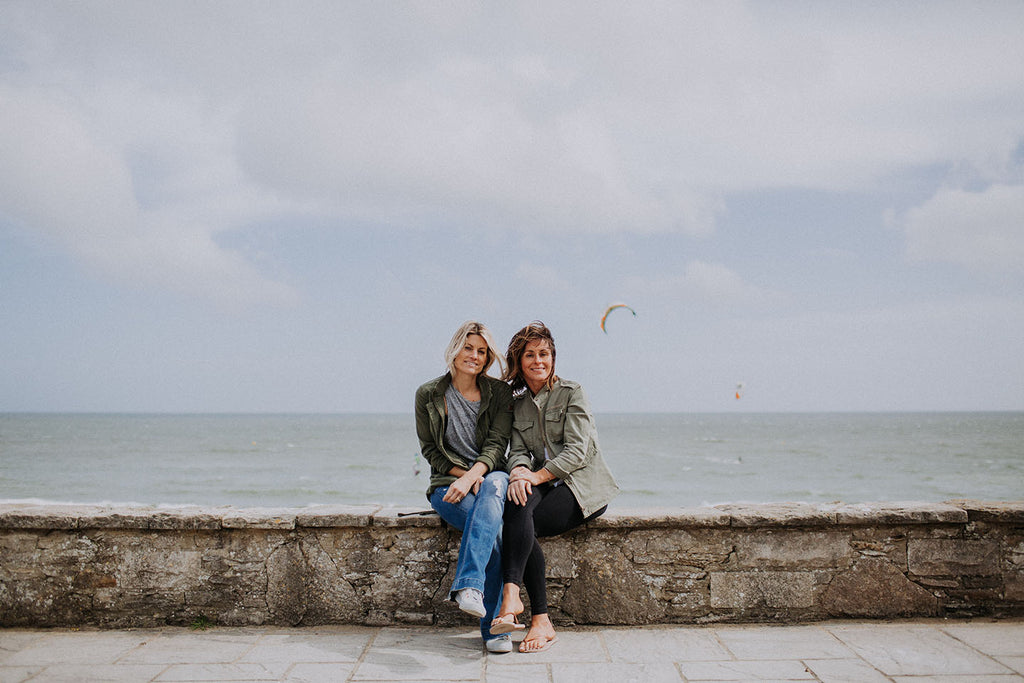 Two women sat on wall by the sea