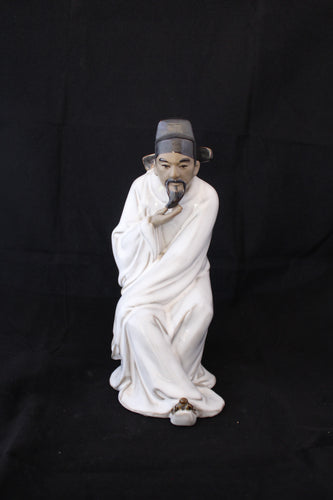 Seated Asian original mud man with black hat
