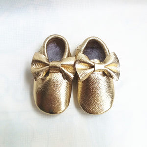 Real leather moccasins with a feminine bow and fringe in metallic gold modern twist