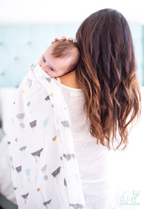 Modern, super soft, breathable, cotton/bamboo muslin baby swaddle features neutral toned mountains sleepy baby comfy