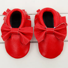 Real leather moccasins with a feminine bow and fringe in red modern twist