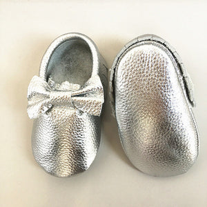 Real leather moccasins with a feminine bow and fringe in metallic silver modern twist