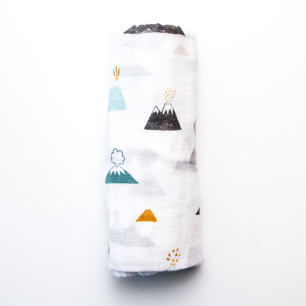 Modern, super soft, breathable, cotton/bamboo muslin baby swaddle features neutral toned mountains cute baby, curious
