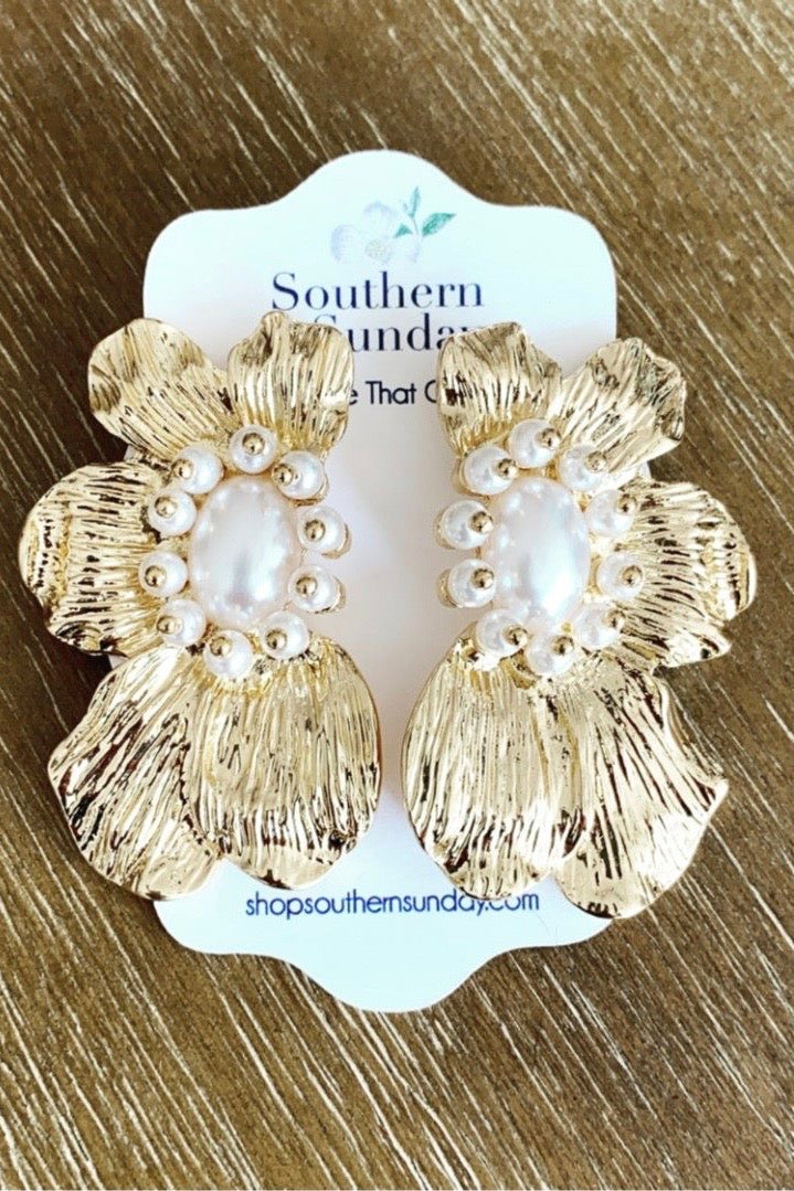 Gold Metal Flower Petal Earring with Pearl Details from Southern Sunday, the boutique that gives back. Southern Sunday offers the latest in ladies fashion and accessories at affordable prices. Southern Sunday also offers a selection of gifts and home decor items. Southern Sunday is located in Midway, KY, outside of Lexington, Kentucky. Shop Southern Sunday online or in store at their boutique.
