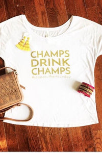 Champs Drink Champs Tee from Southern Sunday, the boutique that gives back.  Southern Sunday offers the latest in ladies fashion and accessories at affordable prices.  Southern Sunday also offers a selection of gifts and home decor items.  Southern Sunday is located in Midway, KY, outside of Lexington, Kentucky.  Shop Southern Sunday online or in store at their boutique.