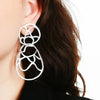 White sculptural double lace statement earrings on model.