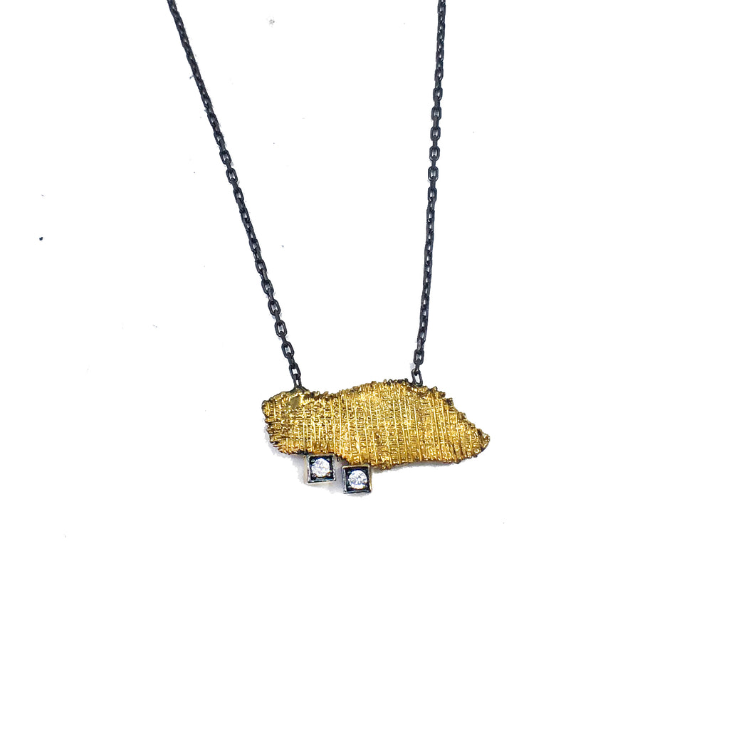 Organic shaped gold brass plated pendant with two cubic zirconia crystals and oxidized sterling silver chain, close up on white background.