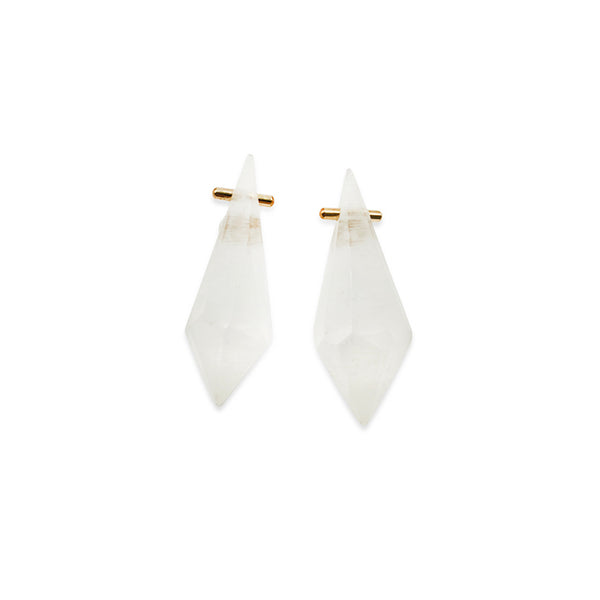 Pair of hand carved white acrylic stones with small gold bars going through them on a white background