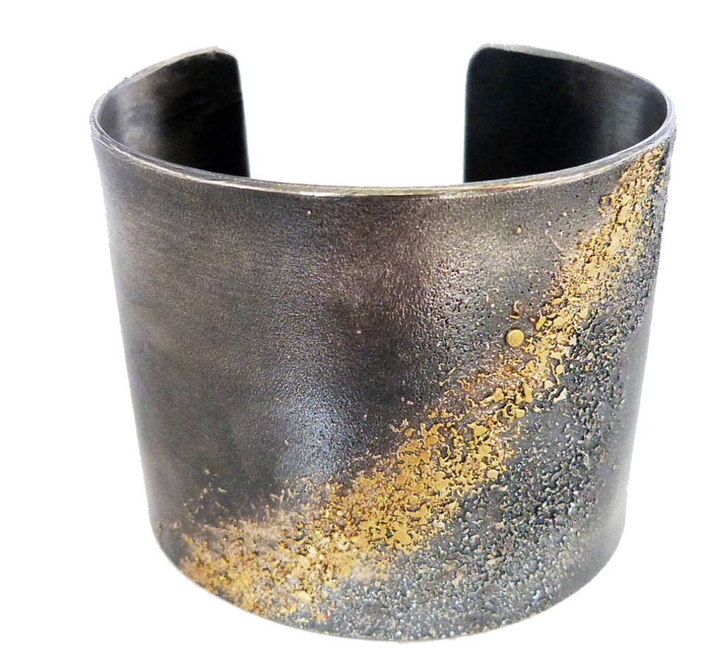 Wide oxidized sterling silver cuff bracelet with speckled gold accents, close up on white background.