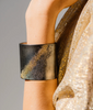 Wide oxidized sterling silver cuff bracelet with speckled gold accents, on model.