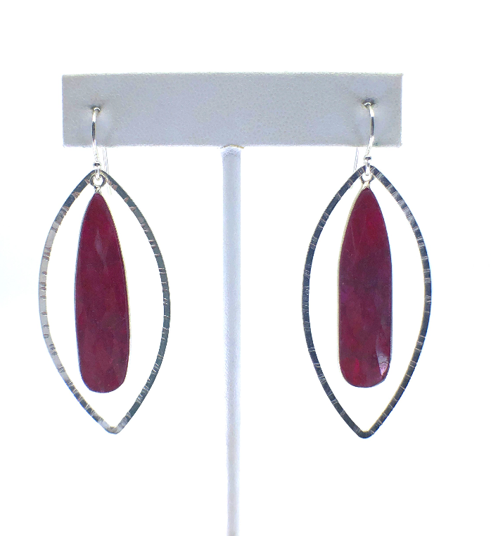 Teardrop ruby and sterling silver dangle earrings, on earring stand with white background.