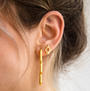 Small zig zag gold stud modeled on an ear, paired with a larger zig zag earring