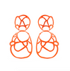 Orange sculptural double lace statement earrings on white background.