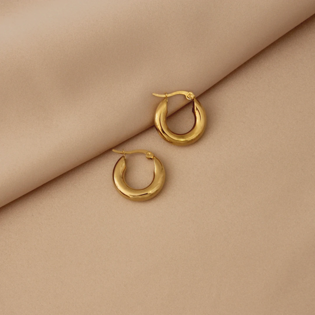 Small classic thick hoops, on tan cloth background.