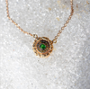 Round 18k yellow gold pendant with tsavorite center stone and autumn color diamond pave, close up on white background.