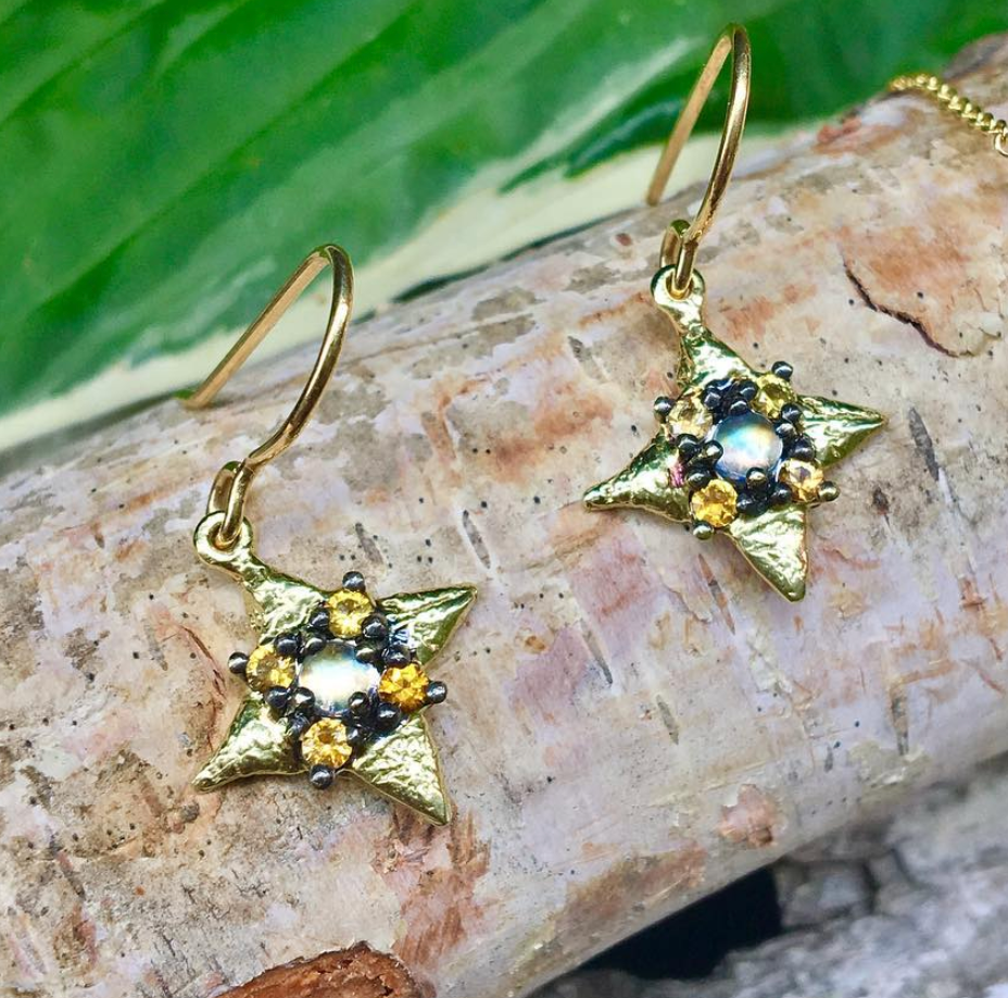 Star shaped gold earrings with moonstone center and orange sapphire accents, displayed on a tree branch.