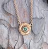 Round 18k yellow gold pendant with tsavorite center stone and autumn color diamond pave, close up on stone background.