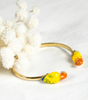 Gold plated brass cuff bracelet with porcelain parrots on each end, on cloth background.