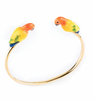 Gold plated brass cuff bracelet with porcelain parrots on each end, on white background.