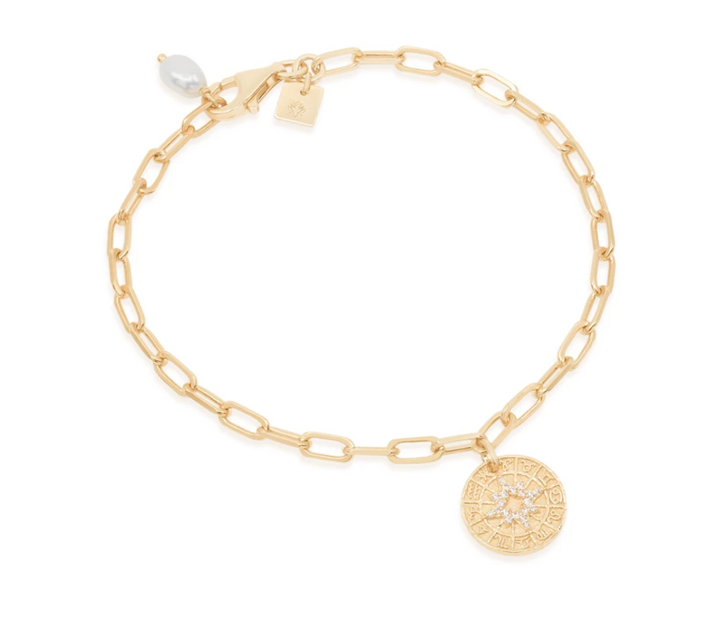 Zodiac wheel charm bracelet with cubic zirconia and fresh water pearl accents, on white background.