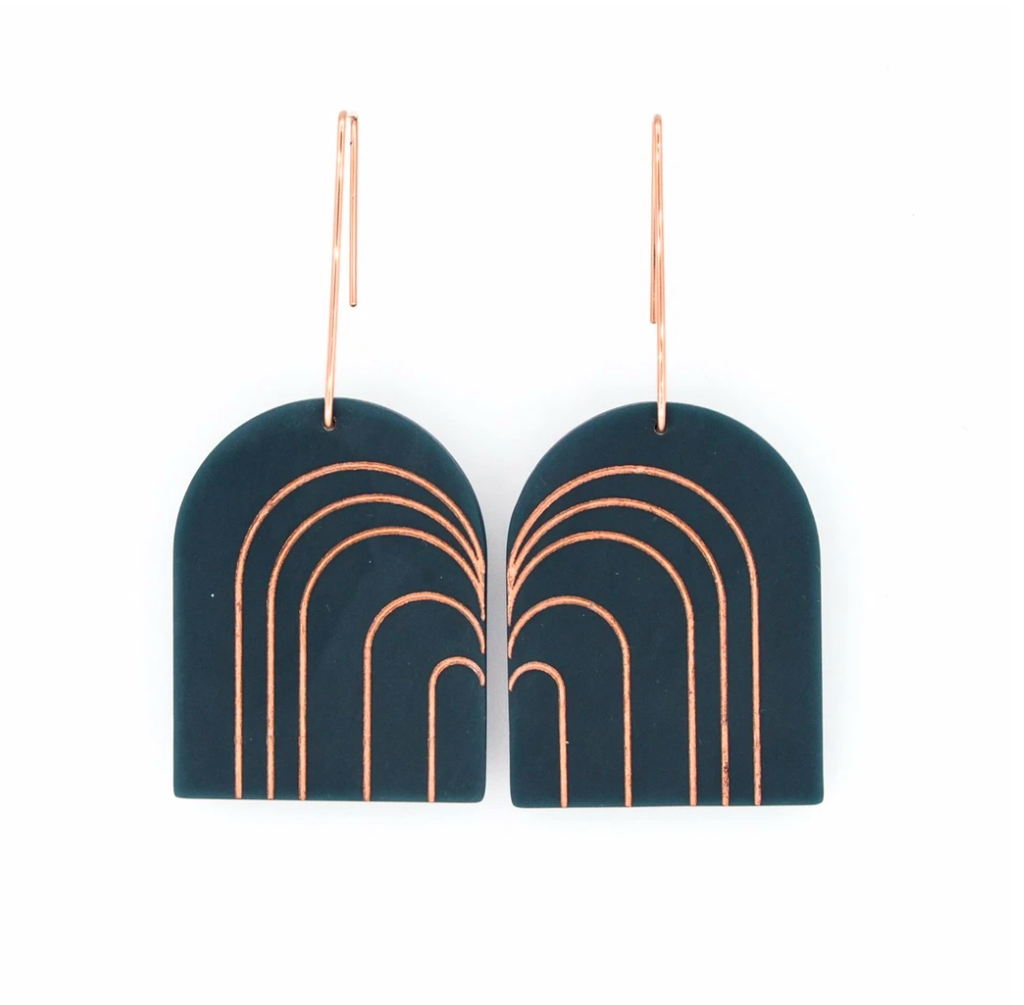Pair of acrylic arch-shaped earring in black with rose gold painted details on a white background