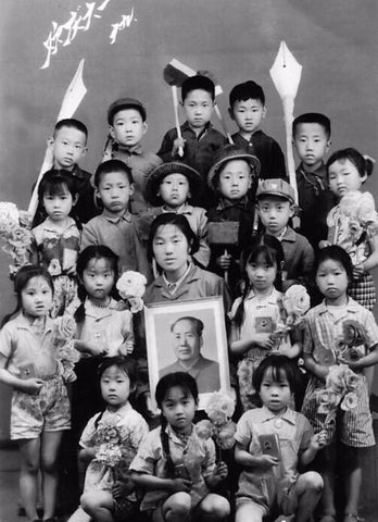 image of children celebrating Children's Day in 1960 with teacher holding a portrait of Mao
