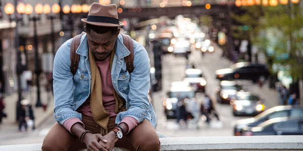 anxious man sat down in the city looking down anxiety symptoms