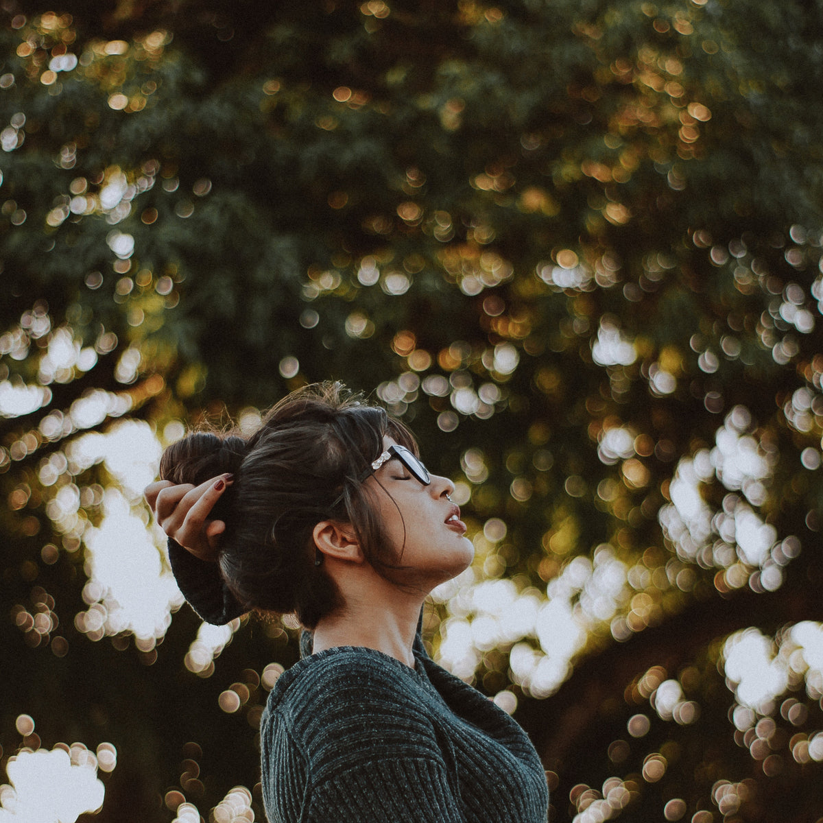 women wearing glasses breathing deeply sign of relief in a park