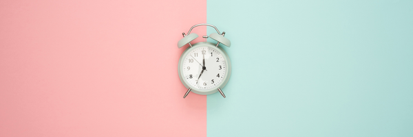 Vintage clock on pink and turquoise background