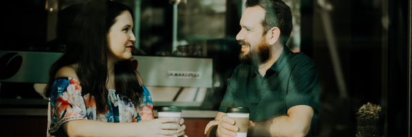 @christinhume Man and Woman having coffee in cafe window, smiling couple