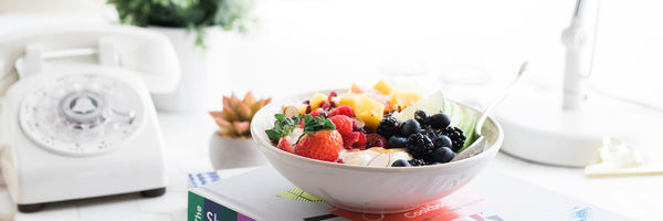 @brookelark healthy breakfast bowl of fruit, strawberries, berries on a busy desk