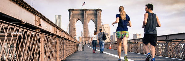 @curtismacnewton man and woman couple jogging on the brooklyn bridge in the day