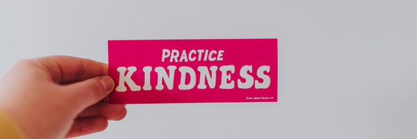 person holding a card that says practice kindness