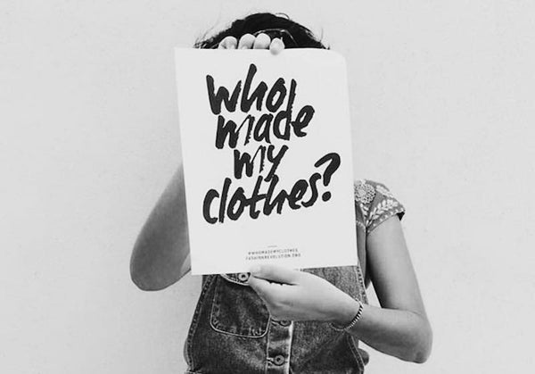 Women holding sign saying who made my clothes