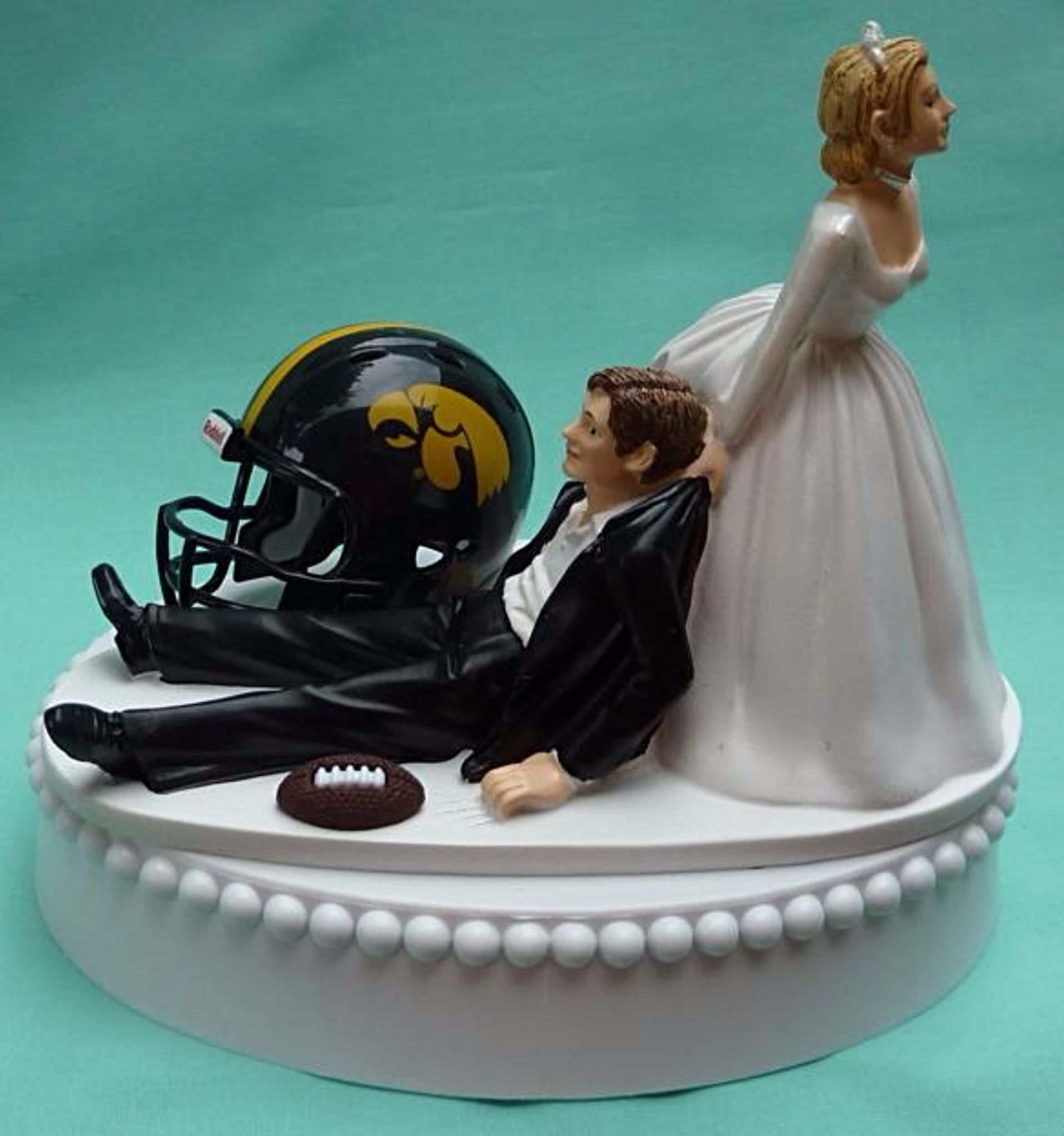 Iowa Hawkeyes wedding cake topper University of Iowa football sports fans funny bride dragging groom humorous ball helmet green turf reception gift Fun Wedding Things