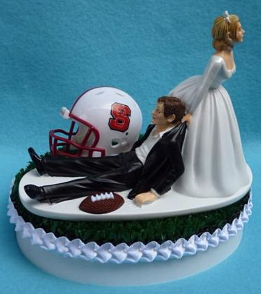North Carolina St. wedding cake topper NCSU Wolfpack State football groom's cake top sports fans funny bride dragging groom green turf helmet ball reception Fun Wedding Things humorous